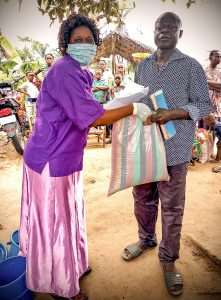 "Pastor ""Jacky"" Ntumba providing a bag of food to a refugee family"
